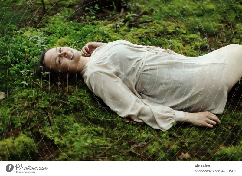 Young woman lying on moss in forest clearing Woman young maiden Moss Forest Ground Woodground pretty daintily Brunette 18 - 30 years 30 - 45 years Long-haired