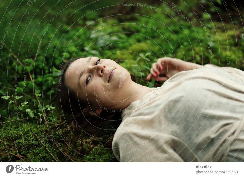 Young woman lying on moss in forest clearing Woman Moss Forest Ground Woodground pretty Graceful Brunette 18 - 30 years 30 - 45 years Long-haired Dress plants