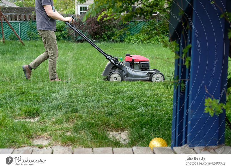 Man mowing tall grass; suburban back yard with deck and landscaping lawn mower lawnmower growth chore weekend exercise home wood garden work green gardening cut