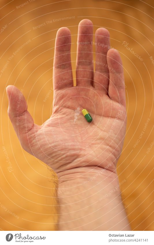 Caucasian male hand holding a medical pill in his palm shallow depth of field man danger safety prevention protective drugs gesture pills object one therapy