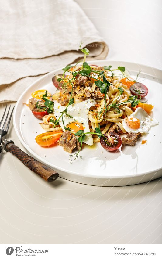 Close-up of delicious homemade spaghetti with vegetables, cheese and fried quail eggs on a round plate on a light background. Traditional Italian food. Mediterranean lunch or dinner. Copy space