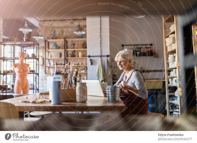 Senior craftswoman in art studio pottery artist ceramics work working people senior adult casual attractive female happy Caucasian enjoying one person beautiful