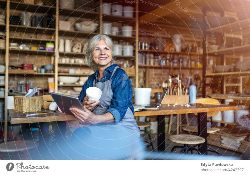 Portrait of senior female pottery artist in her art studio ceramics work working people woman adult casual attractive happy Caucasian enjoying one person