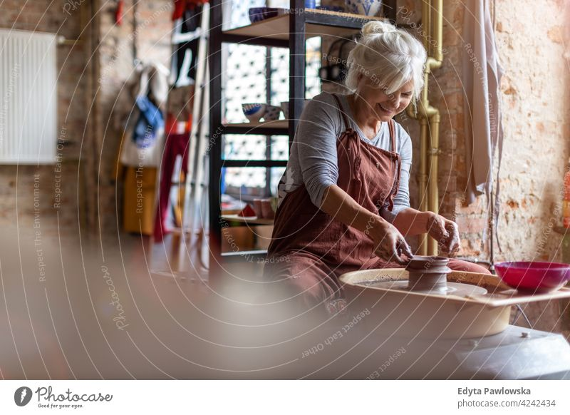 Elderly woman making ceramic work with potter's wheel pottery artist ceramics working people senior adult casual attractive female happy Caucasian enjoying