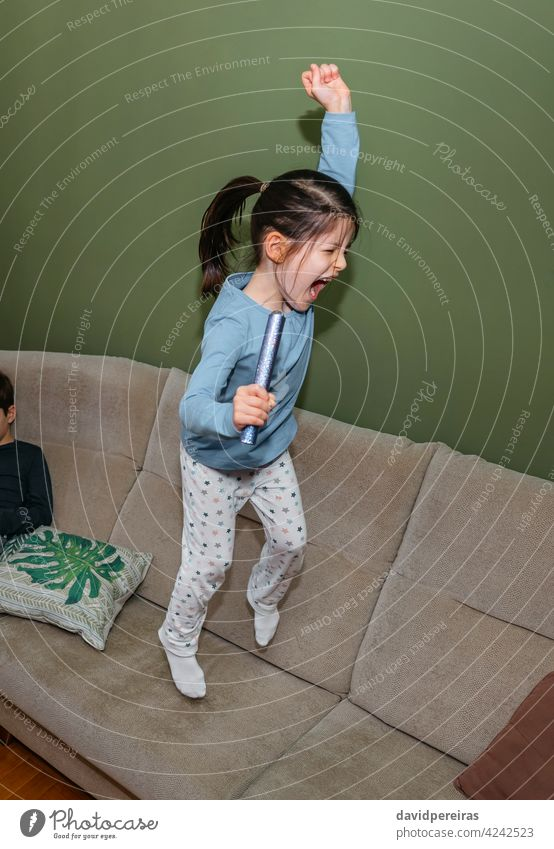 Girl jumping and playing on the sofa girl homewear pajama fun shout couch caucasian happy young people lifestyle cute hyperactive funny happiness joy person