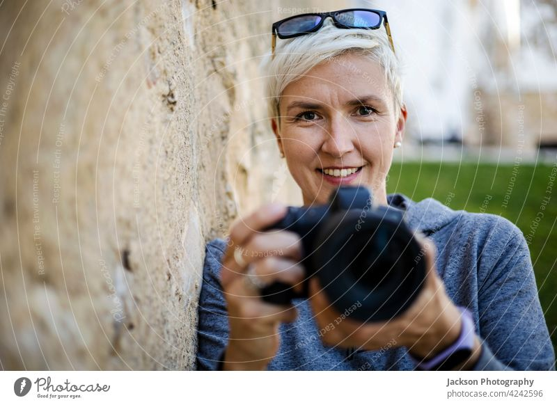 Smiling woman with the digital camera in her hands portrait photographer smile old copy space hoody female glasses positive girl photographer take a photo