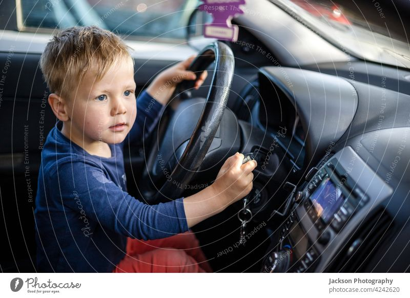 Small boy sitting by steering wheel the car drive fun toddler transport face blond 3-4 preschool window road seat outdoor family funny safety transportation