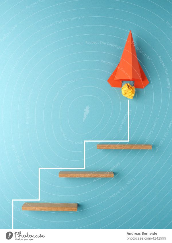 Orange rocket or starship climbing the stairs, upswing or startup concept Rocket crumpled paper ball action goal success financial business blocks message