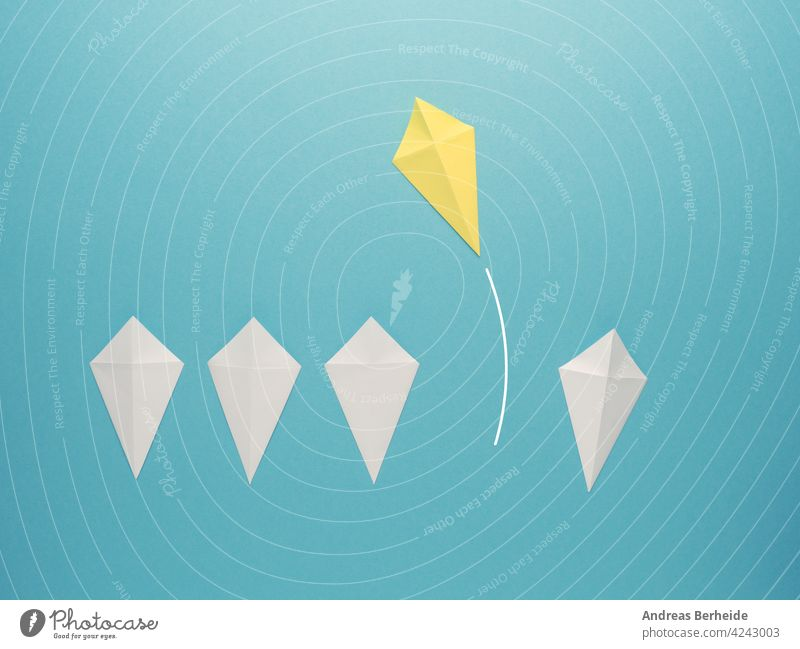 White paper kites in a row with a yellow paper kite flying away leader leadership action goal success financial business message marketing blue management