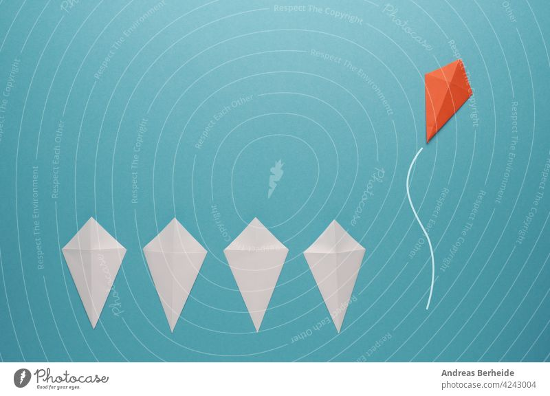 White paper kites in a row with a red paper kite flying away leader leadership action goal success financial business message marketing blue management strategy