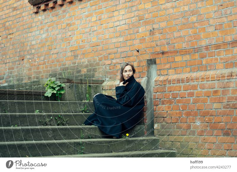the woman sits on a staircase wrapped in a cloak and looks back the way over her shoulder Young woman Coat melancholy Face of a woman Feminine long hair