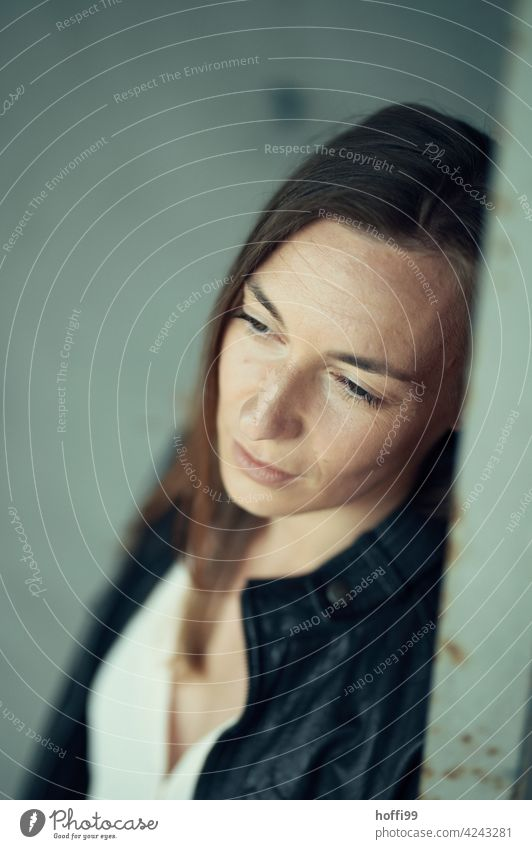 the woman averts her eyes thoughtfully 1 Young woman blurred background Emotions Face of a woman Brunette Women's eyes Think Moody Pensive sad Meditative