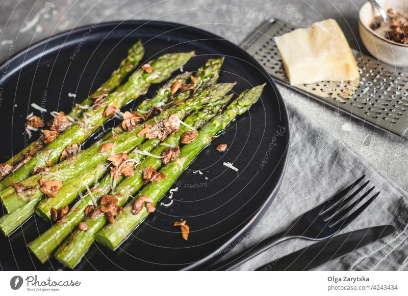 Baked asparagus with almond nut petals and cheese on black plate. baking roasted vegetarian food serving sause cutlery linen napkin gray table angle view