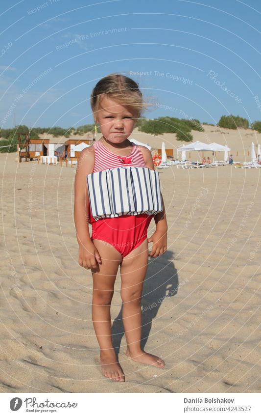 little girl stands on beach in a special swimsuit for children who can not swim. child in swimsuit, which he kept afloat portrait outdoor sun 3 recreation