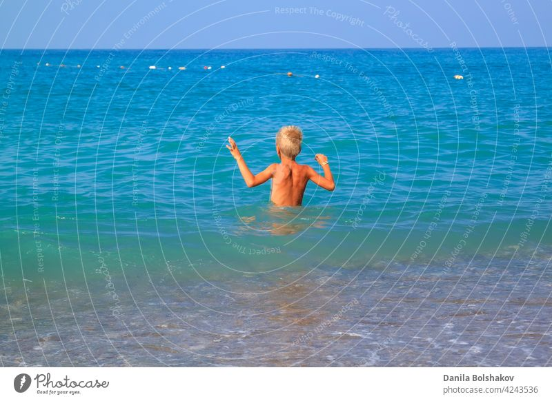 boy enters gently with his hands up into the cold summer sea water kid lifestyle jump splash happy kids fun throw turkey child people vacation beach bright