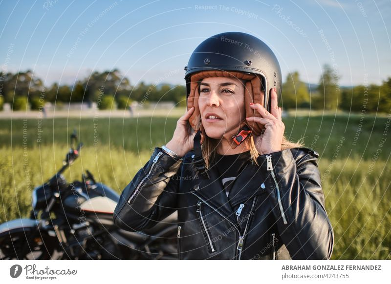 young woman putting on motorcycle helmet person rider vehicle safety transportation motorbike protection countryside motorcyclist road drive trip outside