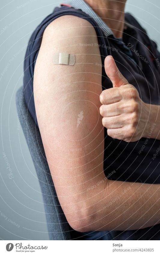 Man with a sticking plaster on his arm and thumbs up Immunization Adhesive plaster coronavirus prevention Healthy Virus pandemic Illness medicine flu Thumbs up