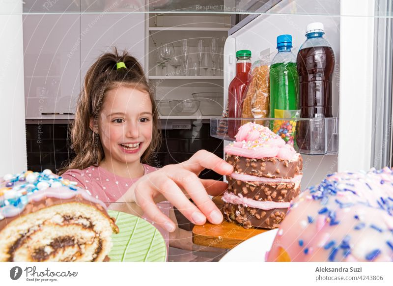 Open fridge from the inside, glass shelves with colourful desserts, cakes, cookies, candies, bottles of sugar drinks. Unhealthy eating, sugar food concept. Little girl with happy smile taking cake
