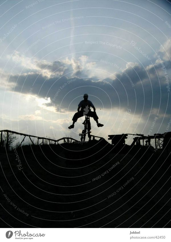 Human being Sky Clouds Dark Movement Jump Bicycle Driving Mountain bike Trick Funsport Clouds in the sky Extreme sports
