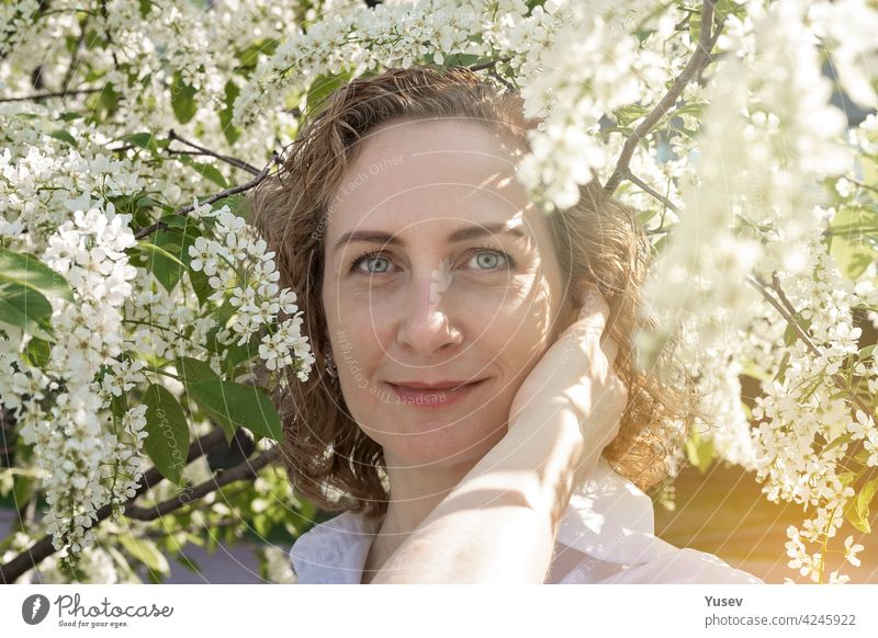 Beautiful smiling caucasian woman with curly hair is posing under a blooming tree. Springtime photoshoot, sunny day. Portrait of a happy woman. Spring sunshine