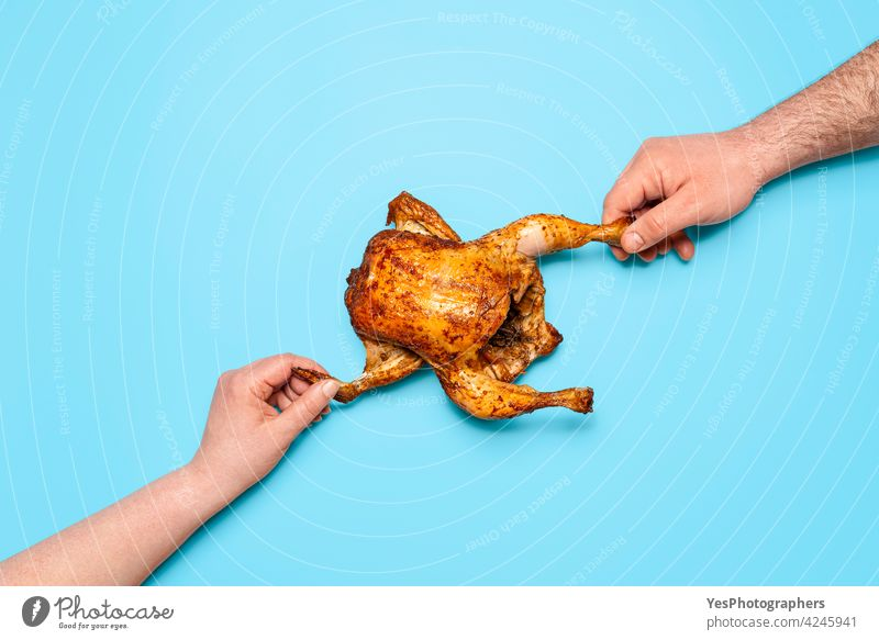 Eating roasted chicken on blue background. People hands grabbing chicken. Sharing food above view baked broiler christmas colored concept consumerism cuisine