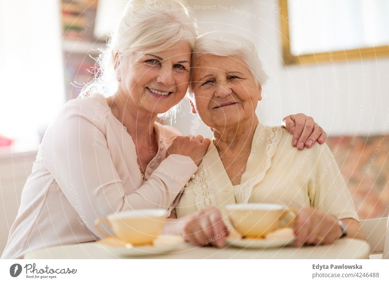 Woman spending time with her elderly mother two people family daughter love assistance trust gratitude help helping support carer home caregiver consoling visit
