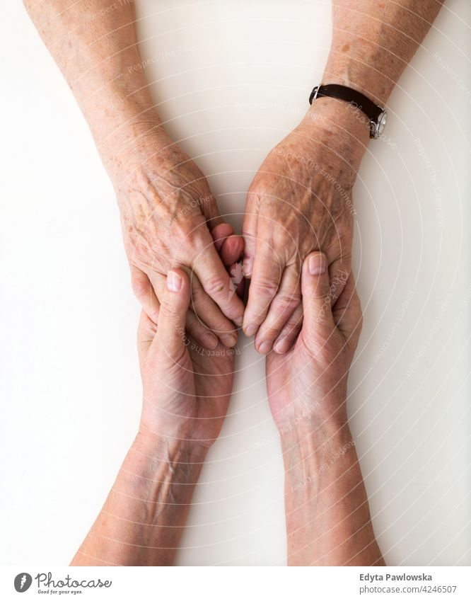Woman holding a loved one's hand in support people woman senior mature casual female Caucasian elderly home house care health healthcare nursing home aging