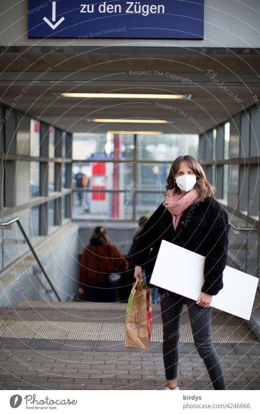 slim young woman with FFP2 mask and luggage at the station. Train traveler Corona virus Mask guard sb./sth. covid-19 corona PUBLIC TRANSPORT trains Arrow