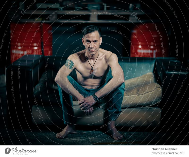man sits on sofa in auto repair shop Man portrait Naked shirtless naked torso jeans Barefoot Auto repair shop Sofa Jewellery Cool Advertising work sexy erotic