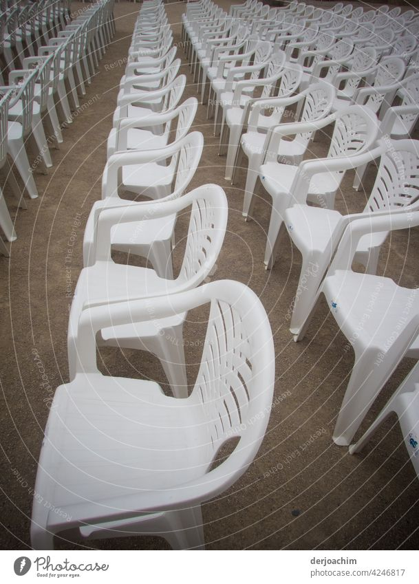 Many white plastic chairs with backrests are lined up next to and behind each other, waiting for the visitors. blocking pandemic Corona Protection Closed White