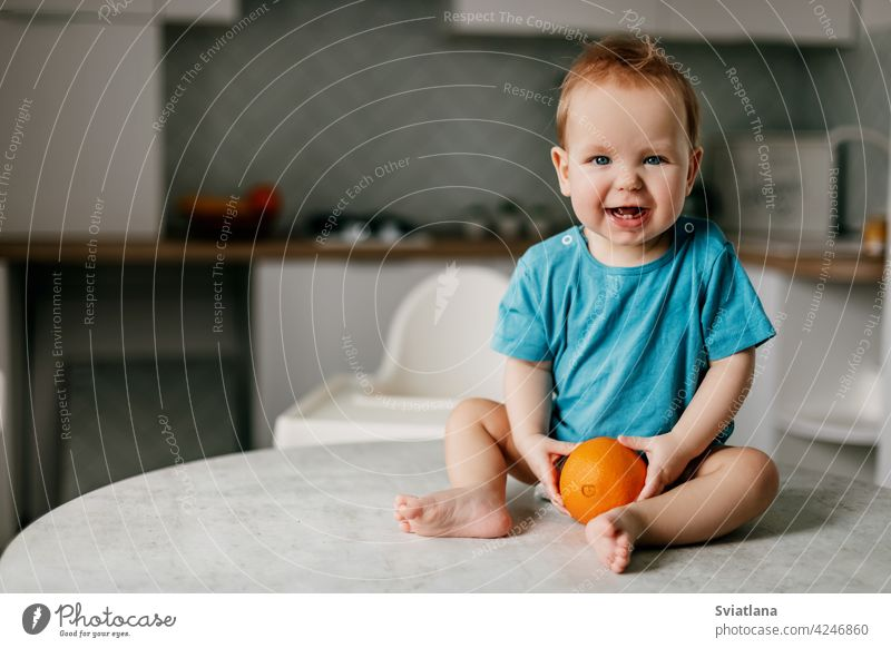 A little boy sits on the kitchen table with an orange in his hands and smiles baby eating kid healthy happy fresh toddler cute food child citrus fruit nutrition