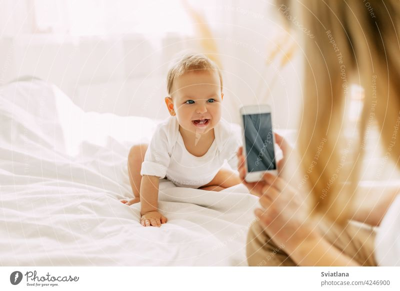 Cute baby is sitting on the bed and posing for his mom, mom is taking pictures of her baby on her mobile phone. Modern technologies, space for text beautiful