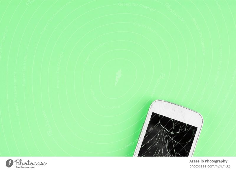 A broken touchscreen cell phone on green background with copy space for text minimal consumer app business call cellular chipset concept consumerism cracks