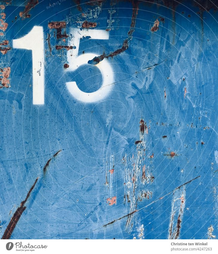 A white 15 on the scratched metal wall of a much used old blue container number fifteen digit Digits and numbers Metal metal facade Container traces of use