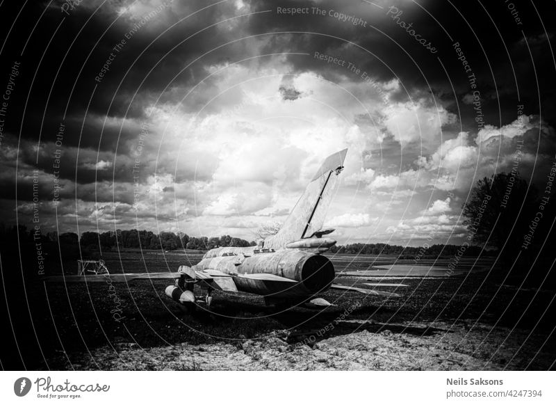 old vintage reactive airplane, plane in the field with dandelions and pond, cloudy dramatic sky in the middle of early may day art background beautiful blue
