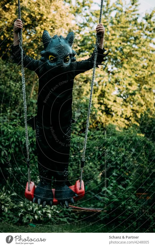 Child standing on the swing dressed as a dragon cladding Dress up carnival Costume Swing Dragon Toothless Black To swing Infancy Family family life Playground