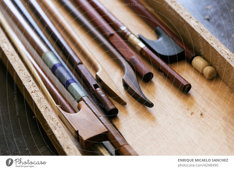 Violin bows in a box in a luthier's workshop string symphony music musical violin instrument artistic bass classical concert entertainment harmony materials