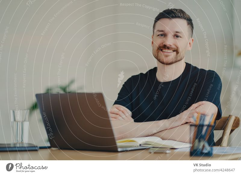 Portrait of happy businessman in casual wear sitting at his workplace in office or home freelancer smiling positive remote work work from home remotely employee
