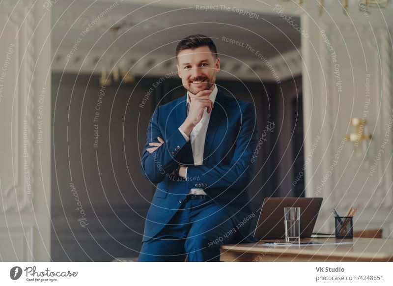 Portrait of smiling confident businessman sitting on office desk laptop handsome looking happy positive young successful modern organized professional work