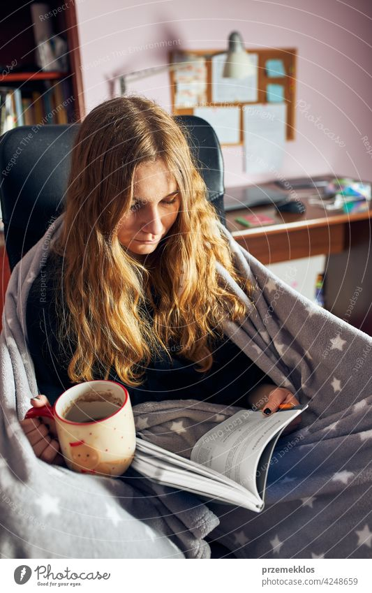 Student learning at home. Young woman making notes, reading and learning from notepad education indoor student working person female notebook studying sitting