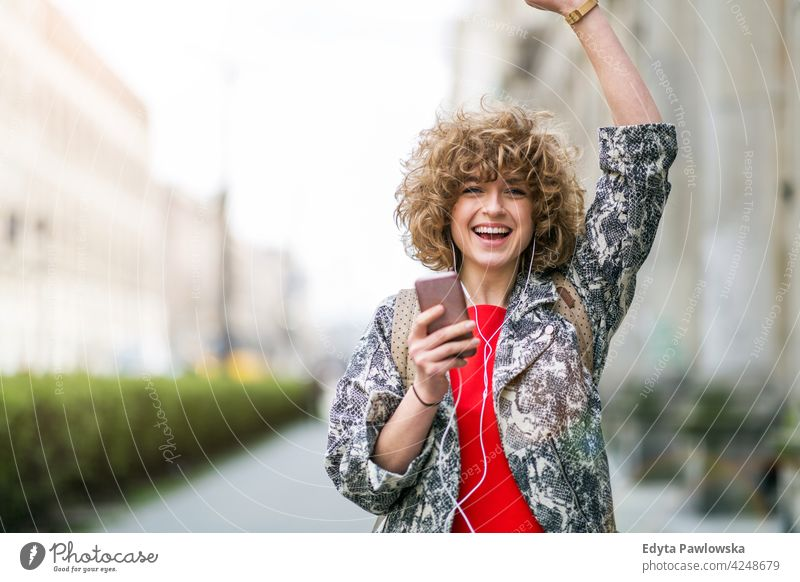Young woman enjoying music outdoors lifestyle young adult people one person casual caucasian positive carefree happy smile smiling female attractive beautiful