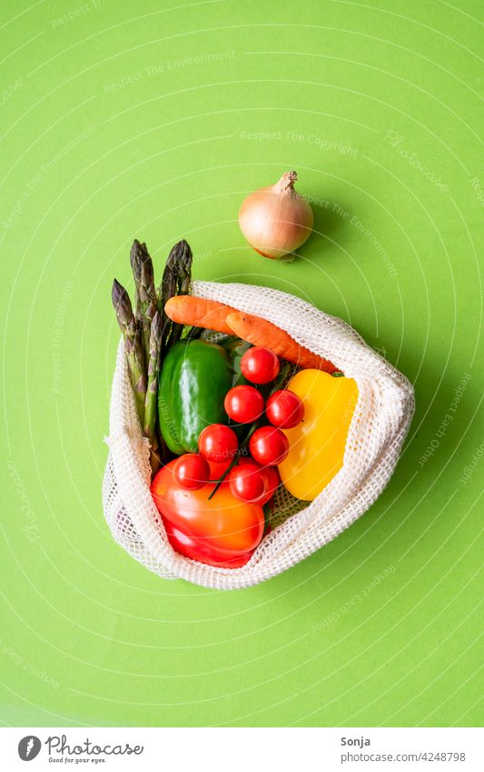 Fresh raw vegetables in a reusable shopping bag on a green background. Top view. Vegetable Raw String bag Reusable Healthy Organic Vegetarian diet naturally