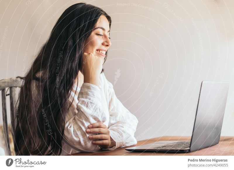 attractive young woman using her laptop in a desk business computer office technology sitting female person work businesswoman beautiful professional girl job