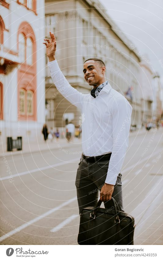 Young African American businessman waitng a taxi on a street american black building cab causal city downtown ethnic guy lifestyle male manager modern one