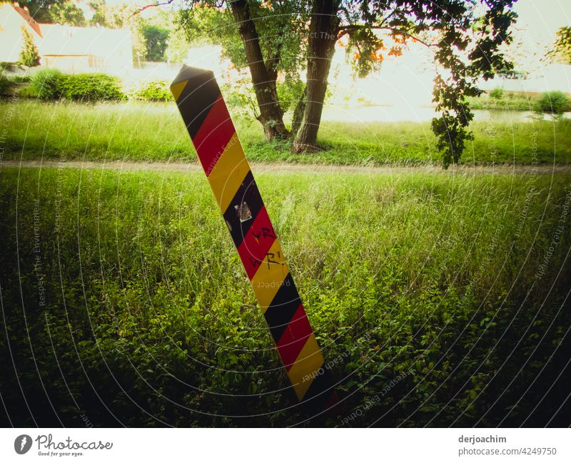 The border post at the river, the Neiße, Germany - Görlitz / Poland, stands quite crooked on the green meadow. goerlitz Pole Park Nature Forest Colour photo