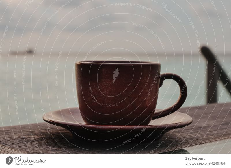A dark brown cup stands on a wooden table in front of the sea, relaxation and tranquility, in muted colors Cup Wood Table Tea Coffee Ocean Looking Horizon