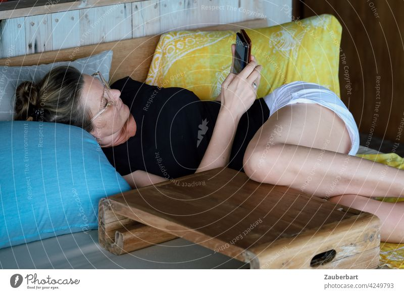 Woman in T-shirt and shorts is lying on a sofa with blue and yellow cushion and wooden table and is reading in her mobile phone feminine Lie tranquillity