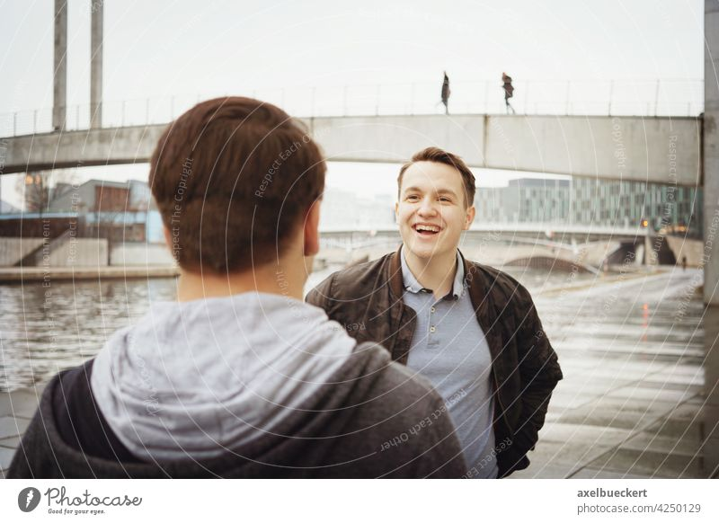 two male teenage friends having a fun conversation by the river candid laughing talking authentic lifestyle real people outside man men smiling friendship young