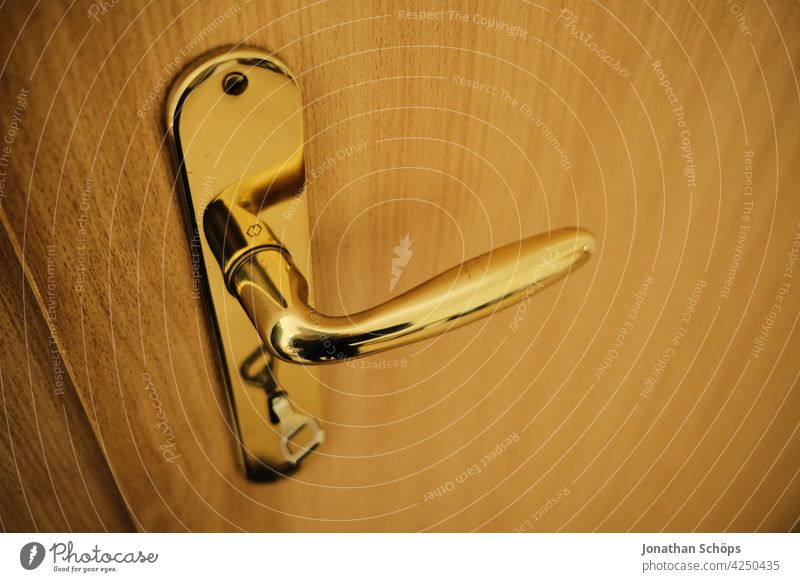golden door handle with key on wooden door in apartment locked Close-up Front door Wooden door Door handle Entrance Closed Deserted Lock Structures and shapes