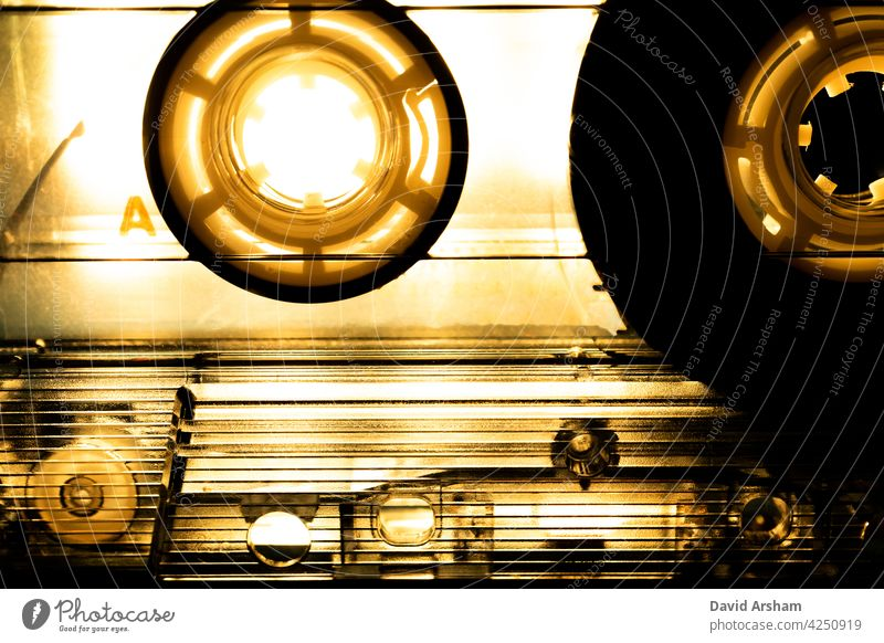 Abstract Closeup of See Through Cassette Tape with Dramatic Sepia Toned Lighting cassette tape reels see through clear music media audio analog hipster vintage